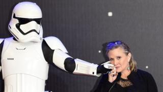 Актриса Кэрри Фишер позирует с имперским штурмовиком