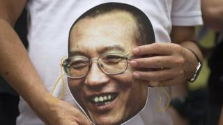Protesters holds a mask with the face of Chinese dissident and Nobel laureate Liu Xiaobo during a protest outside the China Liaison Office in Hong Kong (27 June 2017)