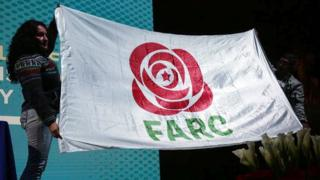 The new logo of the Farc political party, a stylised red rose icon, is displayed on a white flag with the letters FARC, held by two people
