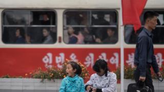 평양 기차역 밖에 시민들이 앉아 있다.