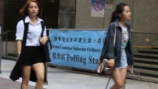 两名年轻女士在香港中环一处投票站外走过(BBC中文网图片11/12/2016)