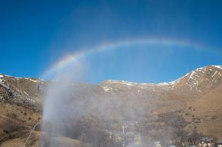 Rainbow in the snow from a snow cannon. The company managing the ski tracks of this ski resort has invested heavily in an irrigation system to feed the snow cannons, which allow skiing when snow coverage is low.