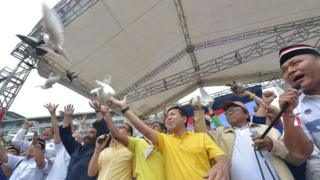 Indonesian parliament speaker Setya Novanto (3 R in yellow) and head of Nasional Demokrat Party Surya Paloh (3 rd L in dark blue) release pigeons as Indonesian people hold a pro-government rally