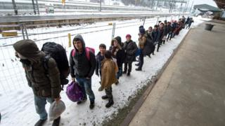 Refugees walk to a chartered train at the railway station of Passau, Germany, on 5 January 2016