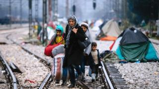 A woman and three children walk on railway tracks connecting Greece with western Europe at the Greek-Macedonian border near the Greek village of Idomeni on 9 March, 2016