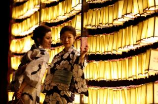 Women in casual summer kimonos take a selfie in front of paper lanterns during the annual Mitama Festival at the Yasukuni Shrine, where more than 2.4 million war dead are enshrined