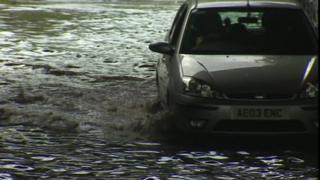 A car driving through floodwater
