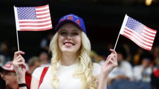 Una mujer sostiene banderas de Estados Unidos