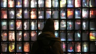 A person looks at Supercube by Stephane Masson on display in St James's Market