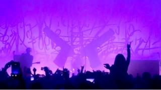 Grab from a video shows guns on stage just before falling