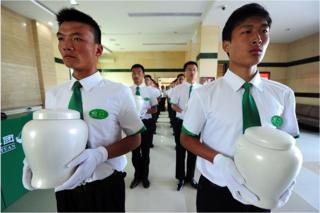 Attendants carry biodegradable urns at a cemetery in Tianjin, northern China, for a collective eco-burial on 20 July 2010.