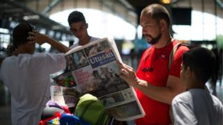 A tourist reads a Malaysian newspaper with reports about the Malaysia Airlines flight MH17 that crashed in eastern Ukraine, at Kuala Lumpur International Airport in Sepang, on July 19, 2014