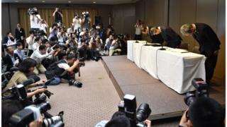 "Глава компании ""Тосиба"" Хисао Танака (у стола, в центре), председатель компании Масаси Мукромачи (у стола, слева) и вице-президент компании Кейдзо Маэда во время пресс-конференции 21 июдя 2015 года."