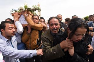Mourners carry the coffin of a victim of the blast at the Coptic Christian Saint Mark's church