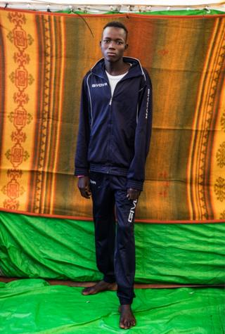 Abdusalam Adam wears a tracksuit and stands in front of a coloured blanket