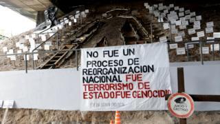 """Monumento que tiene un carte con la inscripción """"No fue un proceso de reorganización nacional. Fue terrorismo de Estado. Fue Genocidio""""."""