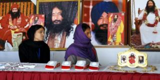 Indian followers of dead guru Ashutosh Maharaj sit in front of posters of him at his ashram on 14 December, 2014