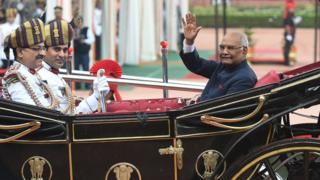 India's new President Ram Nath Kovind waves from a horse-drawn carriage during a ceremony at the Presidential Palace in New Delhi