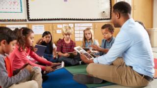 Professor com crianças usando iPad