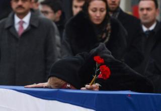 卡爾洛夫的遺孀趴在他的遺棺上哭泣。
