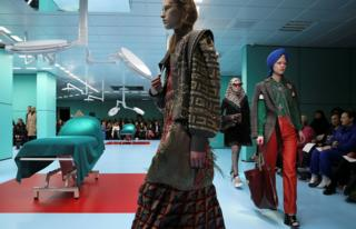 Female models walk down the catwalk next to medical beds