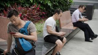 Men on bench staring at phones