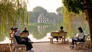 People relaxing on benches by Hoan Kiem Lake