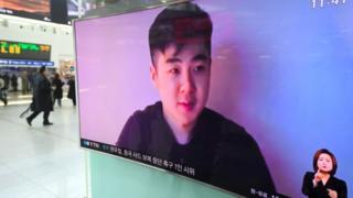 Una pantalla de televisión vista desde la calle en la que se ve el video del supuesto hijo de Kim Jong-nam.