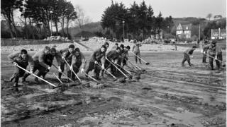 Soldiers clean up oil slick, on April 16, 1967 on the beach of Perros-Guirec