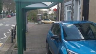 Car parked under bus stop