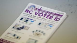 "]A pile of government pamphlets explaining North Carolina's controversial ""Voter ID"" law sits on table at a polling station in Charlotte, North Carolina"