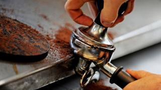 A tamper is used to prepare coffee grounds at the 'Met Cafe', a popular cafe in Sydney