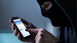 Hooded hacker stealing data on smartphone