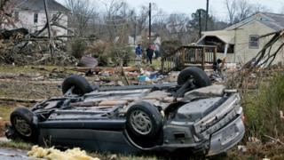 An overturned car rest on a highway next to the foundation of a mobile home that was throw across the highway by a deadly storm that swept through Waverly, Va.,