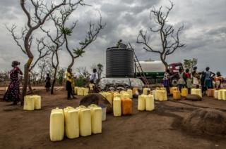 Residents of Rhino camp wait by a water point with the jerry cans, as a tanker offloads its cargo