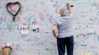 A man writing on a wall in remembrance of those who died at Grenfell Tower