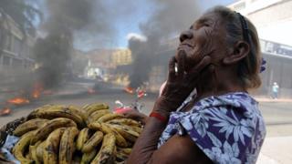 Mujer vendiendo bananos en Tegucigalpa durante una protesta