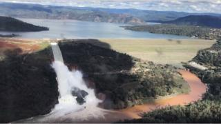 Water flows over an emergency spillway of the Oroville Dam in California, 11 February 2017
