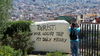 """Barcelona'da bir duvarda """"Turist: Sizin lüks seyahatiniz, bizim günlük eziyetimiz"""" yazıyor."""