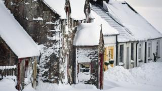 row of cottages under snow