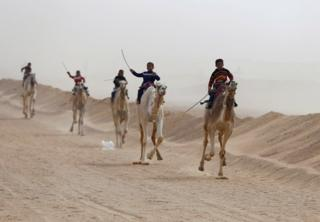 Egyptian children jockeying on their camel mounts during festival at the Sarabium desert in Ismailia, Egypt.