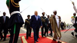 Sudan President Omar al-Bashir (in brown robe) welcomes the President of the Palestinian National Authority Mahmoud Abbas (in suit) to Khartoum Airport in Sudan -19 July 2016