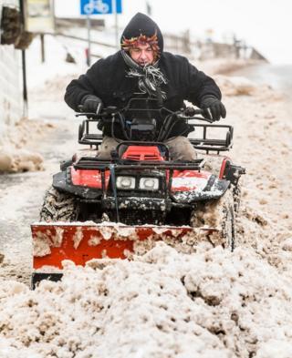 A man clears snow near Blackstone Edge in the Pennines