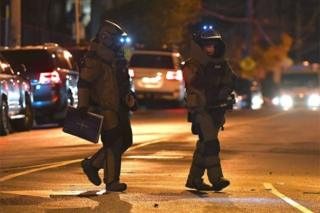 Police from the bomb squad unit walk near scene of the Melbourne siege