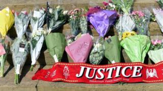 """Floral tributes and a scarf with the word Justice are laid on the steps of St George""""s Hall in Liverpool to commemorate the 96 victims of the Hillsborough disaster on April 27, 2016."""