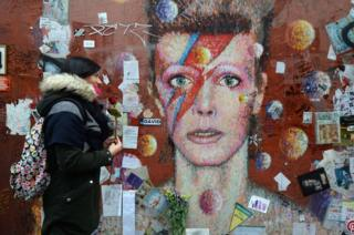 A woman prepares to lay a rose at a mural of David Bowie in Brixton, London.