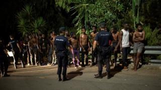 أفراد شرطة يحيطون بمهاجرين نججوا في اقتحام اراضي مدينة سبتة