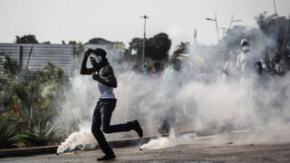 A protester runs amid tear gas canisters during confrontations with the police in Libreville, Gabon on 31 August 2016