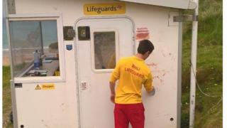 A lifeguard cleans graffiti from a vandalised lifeguard hut