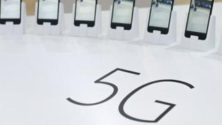 Smartphones positioned next to a 5G sign